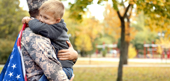 Military man hugging child