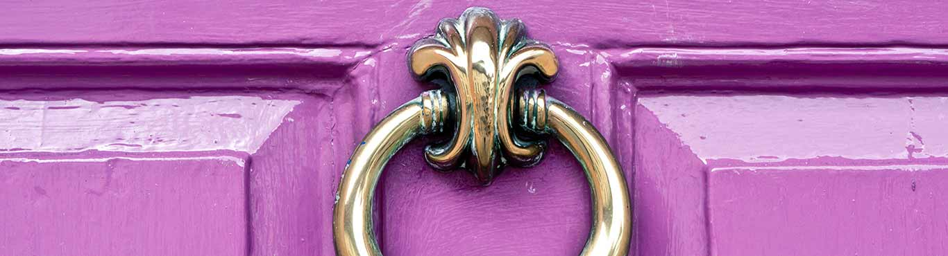 Gold door knocker on a purple door